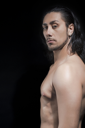 Portrait Of Shirtless Young Man Over Black Background photo