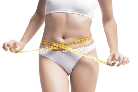 Closeup Of Woman Measuring Her Waistline With Measurement Tape Over White Background