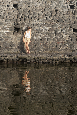 Portrait Of A Young Woman Standing Against Stonewall In Front Of Water photo