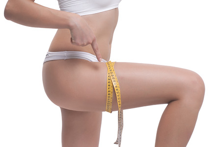 Close-up Of Woman Measuring Her Thigh With A Yellow Metric Tape