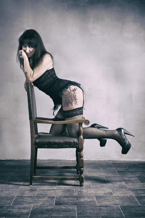 Portrait Of A Sexy Woman Leaning On Wooden Chair