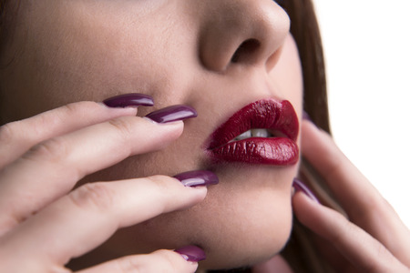 nail varnish: Close-up Of Womans Face With Red Lipstick And Shiny Nail Varnish Stock Photo