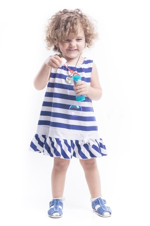 femal: Blonde femal child with soap bubbles and blue dress