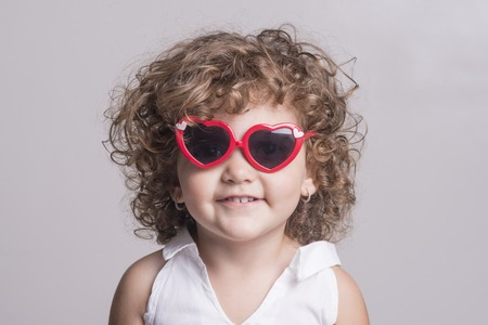 femal: Isolated smiling femal child with red sun glasses over grey background
