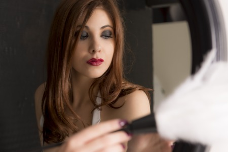 Beautiful Young Maid Holding Brush Cleaning A Mirror frame Stock Photo