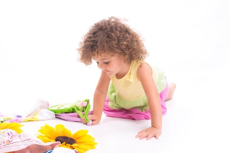 Isolated sweet female child portrait playing on the flor over white background Stock Photo
