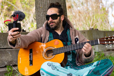 Hippy man with beard and glasses playing guitar making a video herself outdoors on the grass