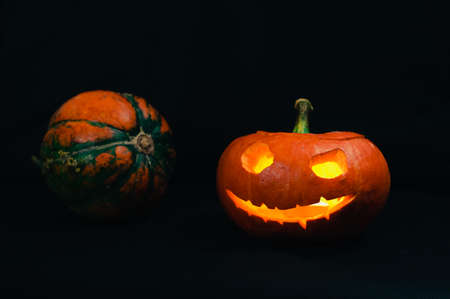 Halloween pumpkin and a small whole pumpkin on the black background 写真素材