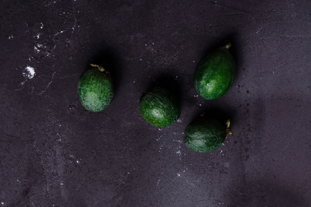 Tropical fruit, raw organic green feijoa on a dark black background, copy space. Healthy food concept