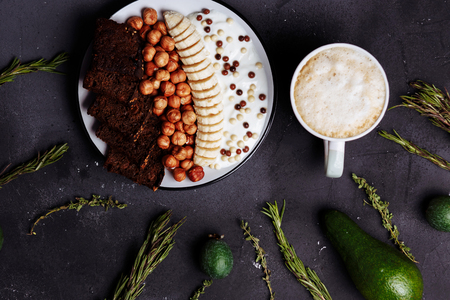 Top view of healthy Breakfast, a Cup of latte or coffee, cocoa, avocado, feijoa, rosemary, cumin on a black background, close up, flat lay Zdjęcie Seryjne