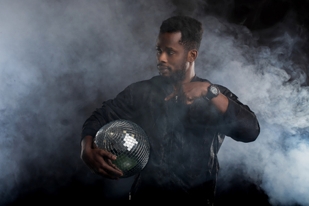 Confident brutal dark skinned man holding disco ball, looking at camera, going to party with friends, wearing casual clothes standing over black background with white smoke. Leisure, lifestyle concept Stock Photo