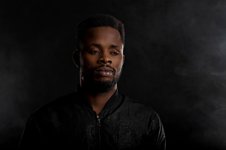 Portrait of attractive young afro man with small beard wearing black jacket looking away with sad and thoughtful expression on dark background with copy space. Human emotions and facial expressions. Imagens