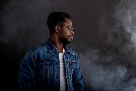 Cool and trendy. Portrait of handsome young African man in glasses wearing denim jacket ad white tshirt looking down while being in front of black background.