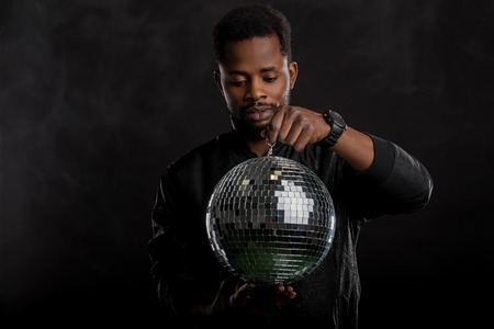 Young cool serious african american man wearing black windbreaker jacket, wristwatches, posing with a disco ball, spending free time in nightclub, standing against white smoke in the dark.