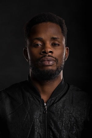Highly detailed closeup portrait of attractive young african man wearing black jacket looking at camera with serious and thoughtful expression on dark background. Human emotions and feelings.