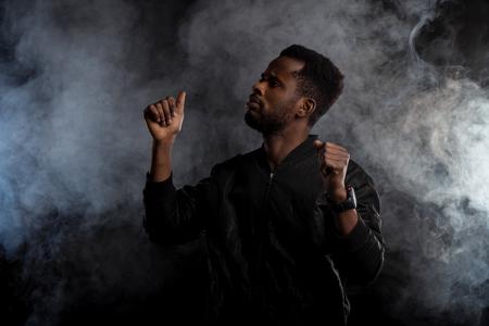 Tiro de cintura para arriba del apuesto joven afroamericano confiado en chaqueta negra con barba gesticulando como bailando, levantando las manos, mirando al lado seriamente contra el humo blanco sobre fondo oscuro.
