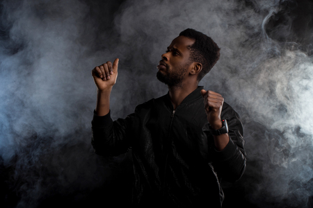 Waist up shot of handsome confident young african american man in black jacket with beard gesturing as dancing, raising hands up, looking to side seriously against white smoke on dark background.