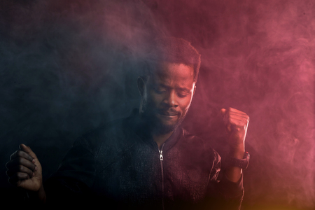 Black man dancing in night club, moving to rhythm of music, raising hands, looking down, enjoying cool music. Portrait relaxed african guy through the smoke in dark. Imagens