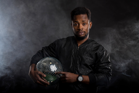 Young cool serious african american man wearing black windbreaker jacket, wristwatches, posing with a disco ball, spending free time in nightclub, standing against thick white smoke in the dark.