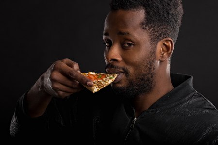 Closeup portrait of hungry unshaven african american guy with piece of tasty pizza in his hand, eating fast food isolated on black background. Unhealthy food, lifestyle, snack. Side view.
