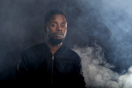 Studio shot of young brutal cool relaxed African man with bread, short curly hair wearing casual jacket standing with closed eyes in dark against white smoke on black background.