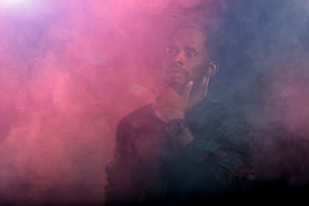 Portrait of brutal attractive black man with beard, full lips, touching chin looking away with thoughtful and dreaming expressions through the pink and blue smoke in dark. Stock Photo