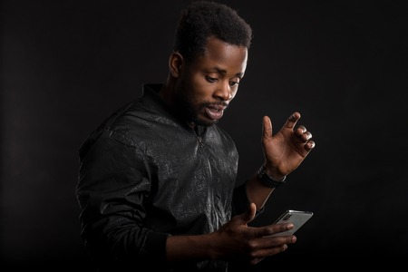 Portrait of shocked and stunned attractive african american man, being confused and surprised while reading news in internet, received unbelievable message standing over black wall. Facial expressions