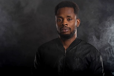 Headshot of serious dark skinned male holding chin looking mysteriously at camera, dressed in black windbreaker jacket, wristwatces, standing against dark background with white smoke. Close up. Standard-Bild