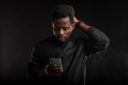 Indoor shot of impressed and amazed attractive African American man with beard and short haircut, holding smartphone, looking surprised at gadget screen with open mouth in dark. Emotions, technology. 免版税图像
