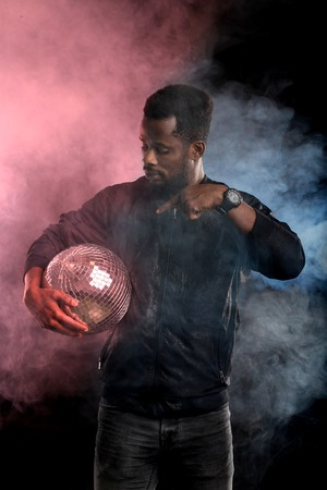 Young cool black man with disco ball over black background. Vertical portrait of african american guy through the pink and blue smoke in dark. Entertainment, leisure, people and lifestyle. Imagens