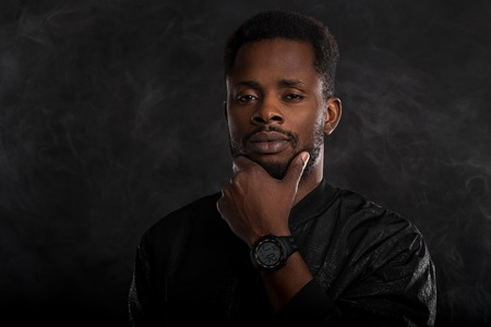 Headshot of serious dark skinned male holding chin looking mysteriously at camera, dressed in black windbreaker jacket, wristwatces, standing against dark background with white smoke. Close up. Stock Photo