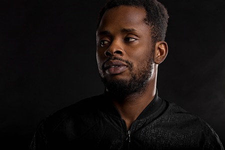 Highly detailed closeup portrait of attractive young african man wearing black jacket looking at camera with serious and thoughtful expression on dark background. Human emotions and feelings. Imagens