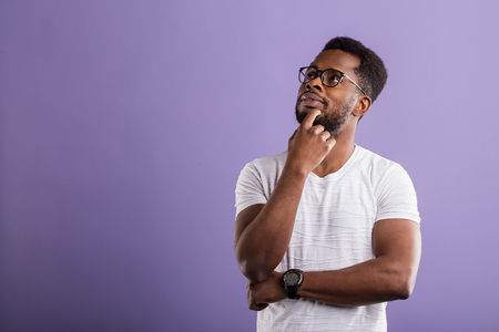 Dark skinned unshaven man with short curly hair in casual outfit holding chin with hand, looking up with dreaming expression, smiling, thinking about something pleasant on violet background.Copy space