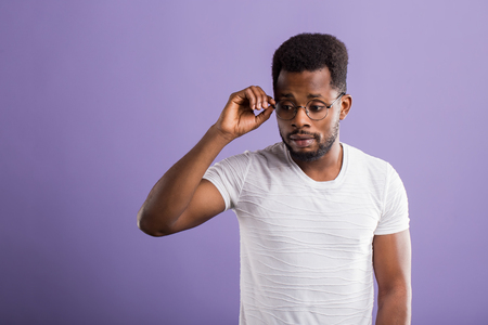 Wow, Its incredible. Close up portrait of young bearded dark skinned man touching the spectacles and looking down with amazed shocked expression against violet background.