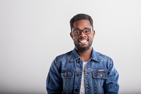 Horizontal close up portrait of joyful happy african guy in spectacles denim jacket smiling broadly with teeth laughing looking at camera over gray background. Facial expressions and emotions concept. 免版税图像