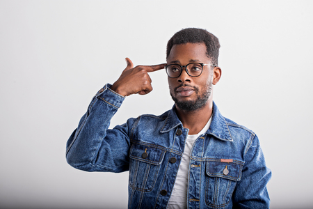 Shot of serious tired attractive black man shooting in temple with index finger, demonstrating suicide gesture, pretending killing himself wearing denim jacket, glasses isolated over white background.