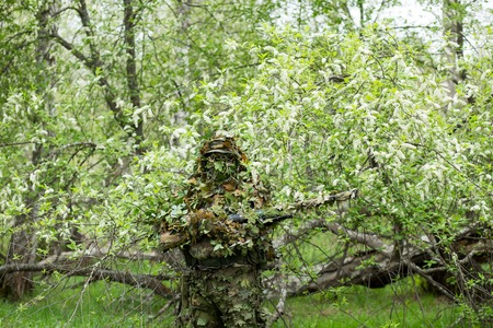 Male sniper posing in green camouflage camouflage clothing with a gun, a rifle on hand in the forest near the cherry blossoms. Army, military, airsoft, hobby concept