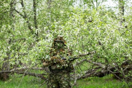 Tireur d'élite masculin posant dans des vêtements de camouflage vert avec une arme à feu, un fusil à portée de main dans la forêt près des cerisiers en fleurs. Armée, militaire, airsoft, concept de passe-temps