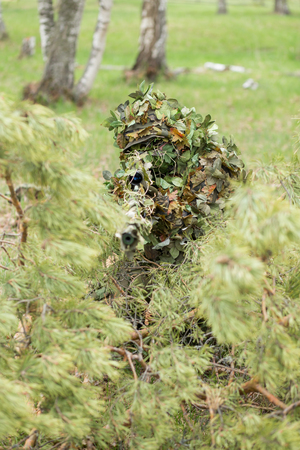Closeup of young camouflage soldier or sniper holding rifle and shoots through green trees Standard-Bild