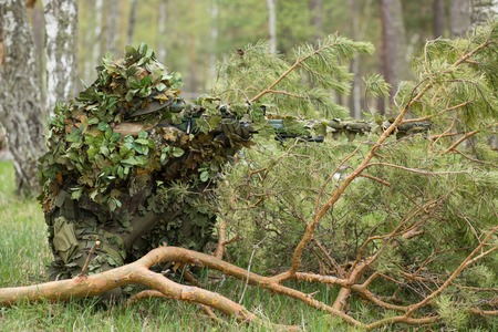 Camouflaged sniper in the forest in ambush. Military man aiming a gun, a rifle at the enemy in nature. Army, airsoft, hobby, game concept
