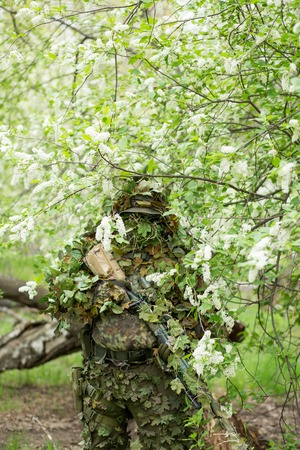 Cute portrait of a military male sniper in camouflage, mask, cap and rifle on his hands against the background of a flowering cherry in the summer outdoors