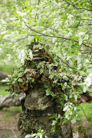 Spring portrait of a military sniper man in camouflage, mask, cap shooting at the enemy in the summer in nature near the white flowering trees. Army, military, airsoft, hobby, game concept 스톡 콘텐츠
