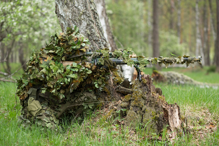 Camouflaged sniper in the forest in ambush. Military man aiming a gun, a rifle at the enemy in nature Stock Photo