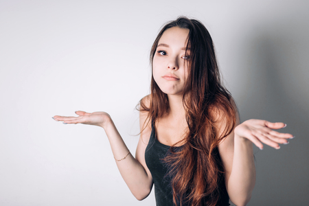 Closeup portrait puzzled clueless young woman with arms out asking what is problem who cares so what I dont know. Negative human emotion face expression reaction perception