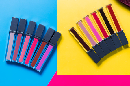 different shades of lipsticks, pink, red, maroon, light and dark blue, yellow background, top view, close up