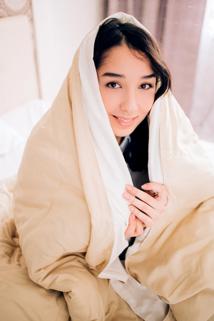 Attractive smiling caucasian woman with natural makeup sitting in bed wrapped in cotton cream color blanket and looking to camera at home. I'm feeling cozy. Rest, relax, morning, bedding concept.
