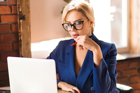 Closeup portrait of young pretty blonde business woman in glasses wearing stylish blue jacket, working on white laptop in cafe, holding pen, seriously looking at screen, making financial report.