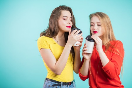 Two smiling students girls drinking morning coffee, inhale the aroma of coffee. Pleasure, relaxation, happiness concept Stock Photo