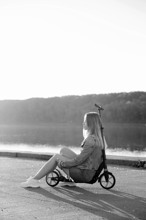 Girl on a scooter by the river. Black and white photo