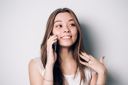 Happy woman phone talking. Face with toothy smile, isolated over white background. Expressive facial expressions